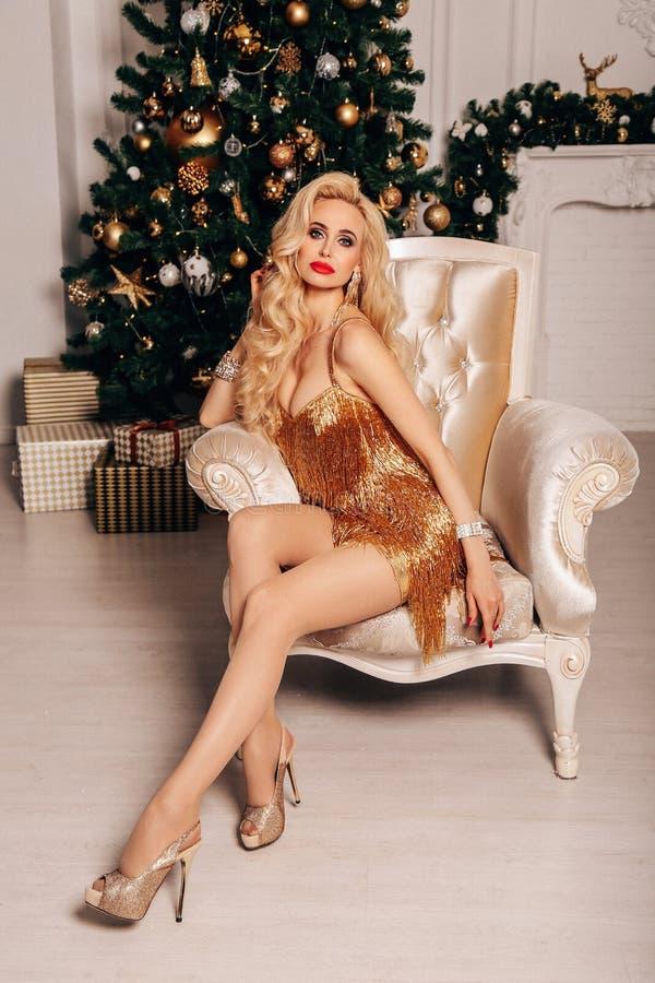 有长的金发的美女在摆在装饰的圣诞树附近的庄重装束 免版税库存照片