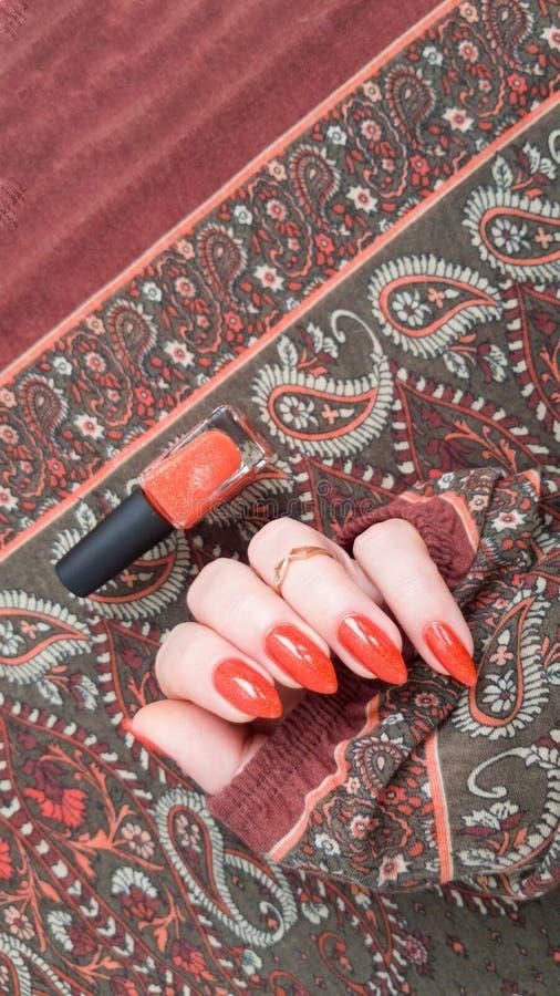 有长的钉子的女性手与金黄橙色指甲油 库存图片