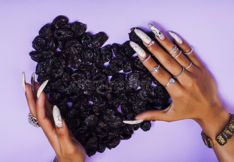 有长的钉子的妇女手修剪拿着在心脏形状的果子在紫色背景的 图库摄影