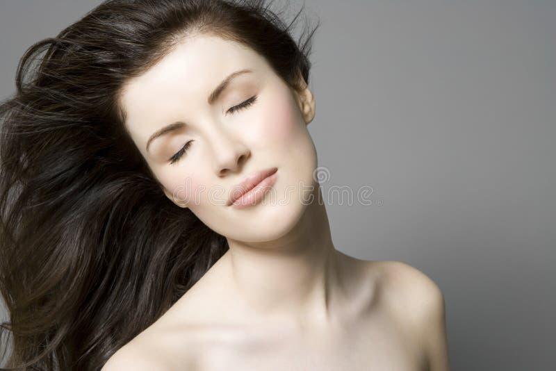 有长的闭上的布朗头发和眼睛的妇女 库存照片