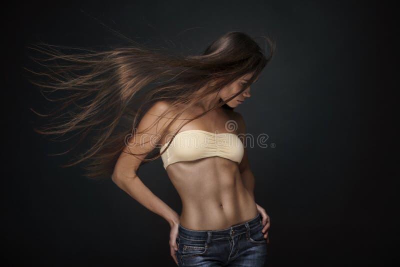 有长的飞行头发的美丽的年轻运动深色的妇女 库存照片