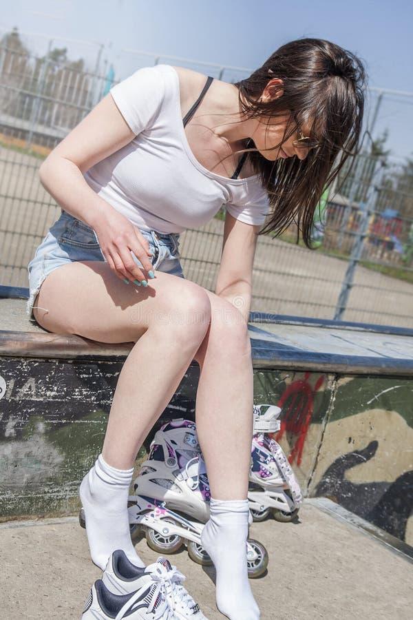 有长的黑发佩带的溜冰鞋的十几岁的女孩 免版税图库摄影