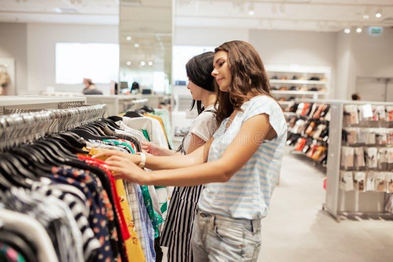 有长的黑发的,佩带的便装样式两个悦目微笑的亭亭玉立的女孩,有购物在一个现代购物中心 免版税库存图片