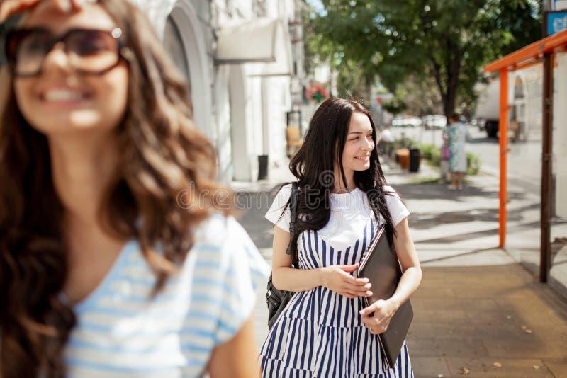 有长的黑发的,佩带的偶然成套装备,在街道下的步行两美丽的少女在一好日子, 免版税图库摄影