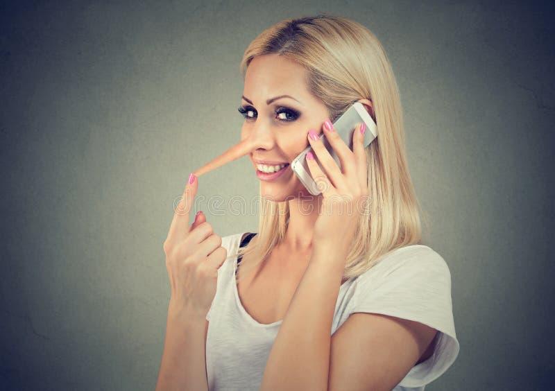 有长的鼻子的愉快的年轻说谎者妇女谈话在手机 库存照片