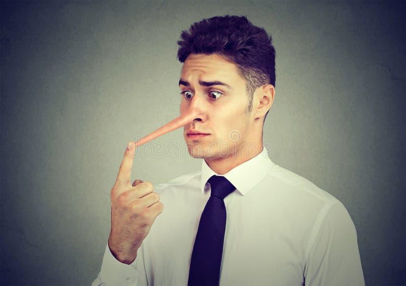 有长的鼻子的担心的年轻商人 说谎者概念 库存图片