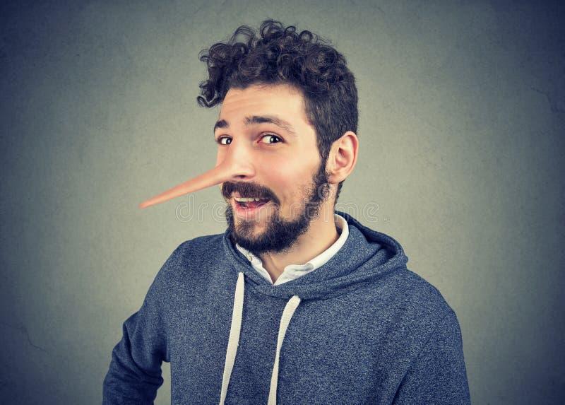 有长的鼻子的说谎者人在灰色背景 库存图片