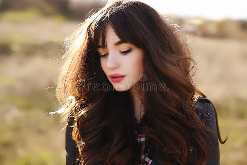 有长的黑健康头发的愉快的美丽的少妇享用新鲜空气和太阳轻室外在日落 免版税库存照片