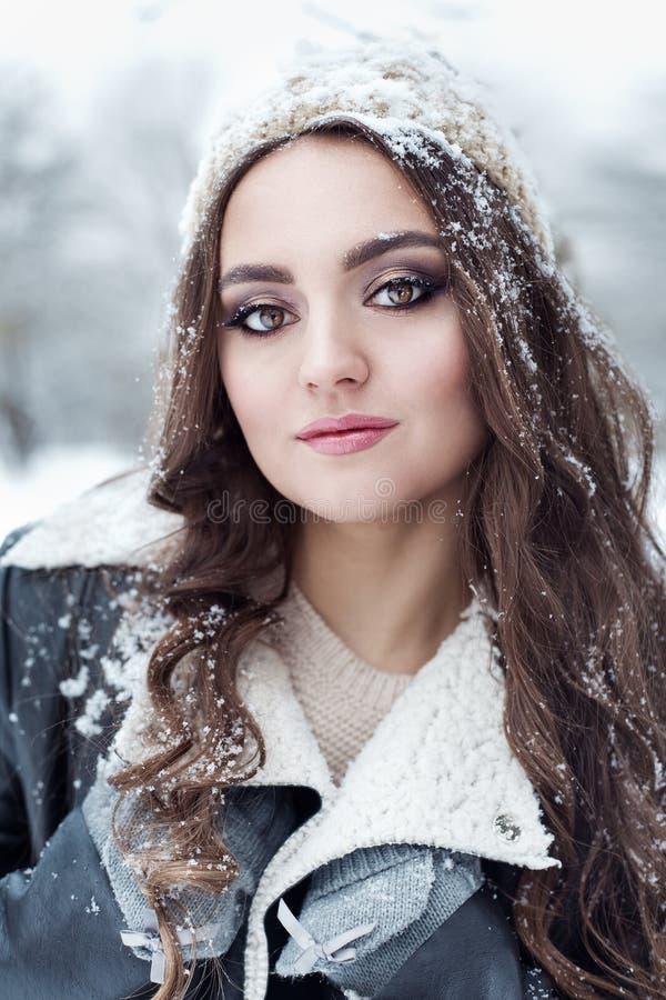有长的黑发乐趣步行的美丽的少妇在冬天森林和使用与在一个冬天帽子的雪在一件黑夹克 免版税库存图片