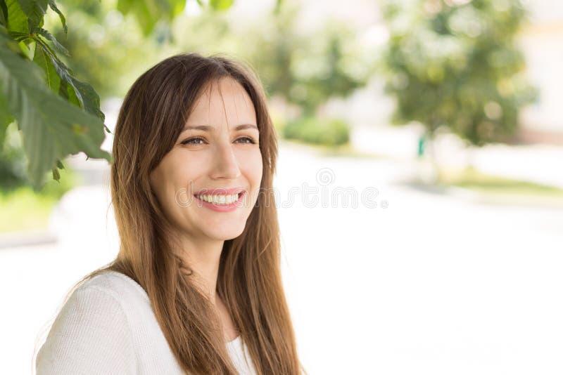 有长的头发和健康牙的美丽的微笑的女孩 免版税库存图片