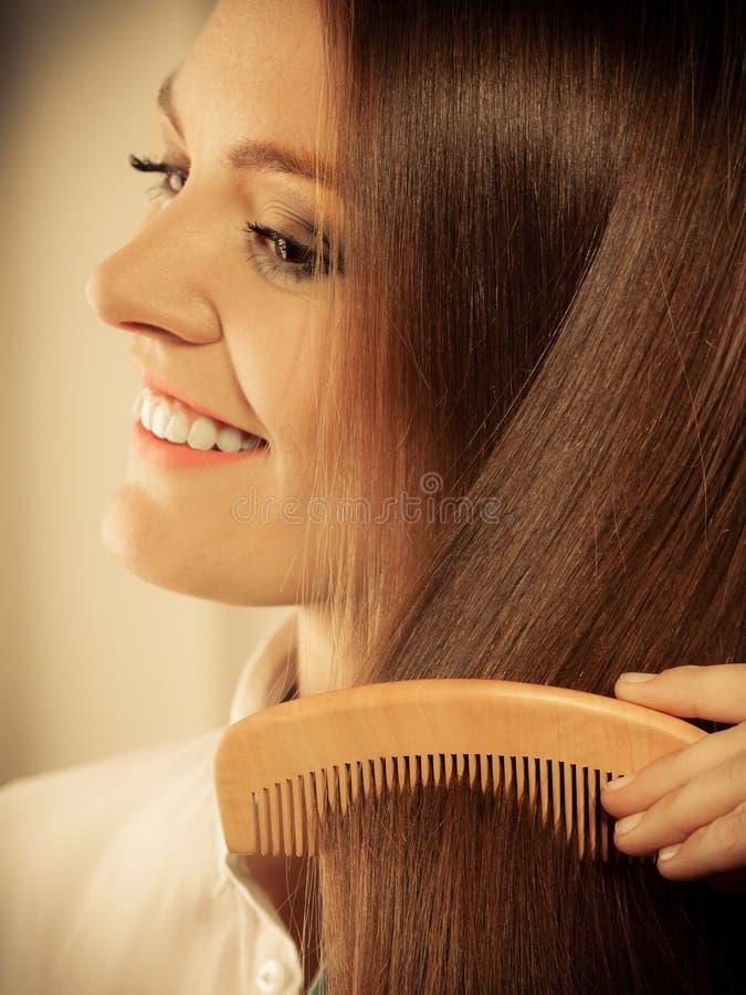 有长的头发和梳子的美丽的妇女 库存照片