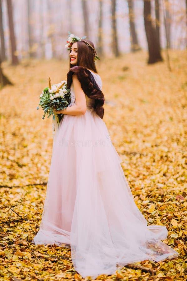 有长的黑发和花圈的华美的新娘走在秋天森林的 免版税库存照片