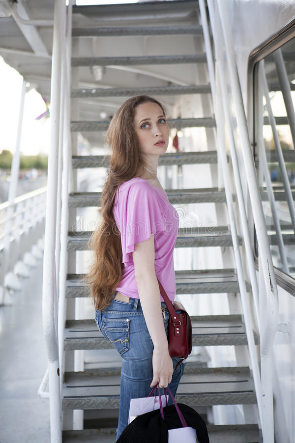 有长的头发和蓝眼睛的严肃的哀伤的妇女,佩带桃红色T 免版税库存照片