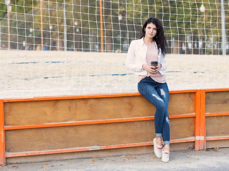 有长的头发浅黑肤色的男人的美丽的高女孩牛仔裤的在与一杯咖啡的体育法院附近坐一个温暖的夏天晚上 免版税库存图片