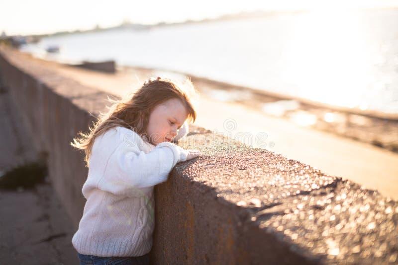 有长的头发的哀伤的女孩临近河,童年 图库摄影