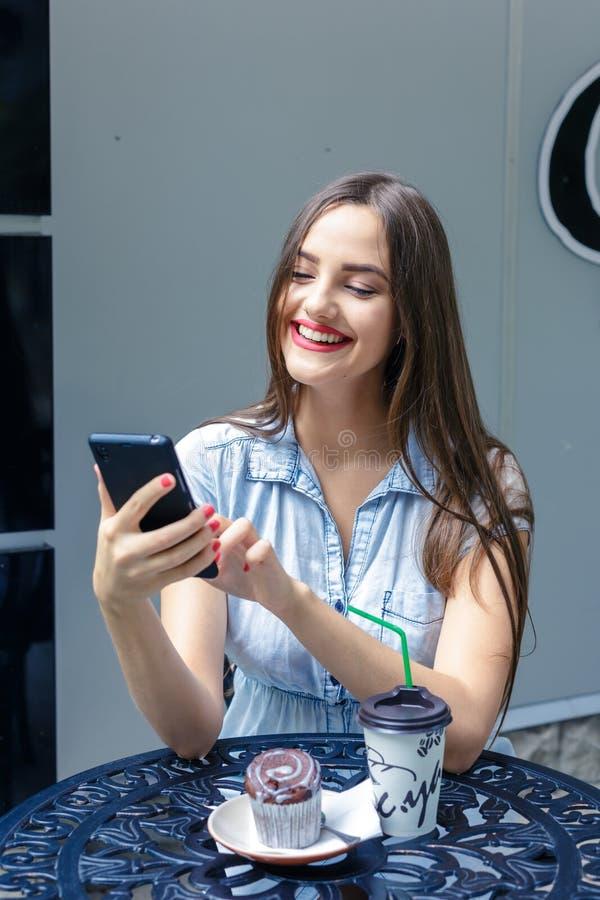 有长的头发的微笑的女孩使用在室外咖啡馆的智能手机 库存照片