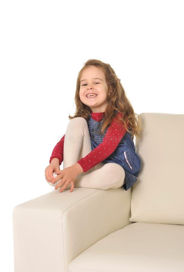 有长的头发的愉快的可爱的小女孩坐长沙发的胳膊 免版税库存图片