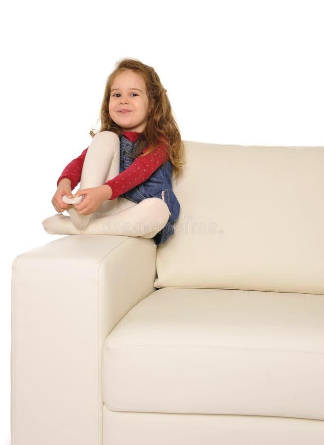 有长的头发的愉快的可爱的小女孩坐长沙发的胳膊 免版税库存照片