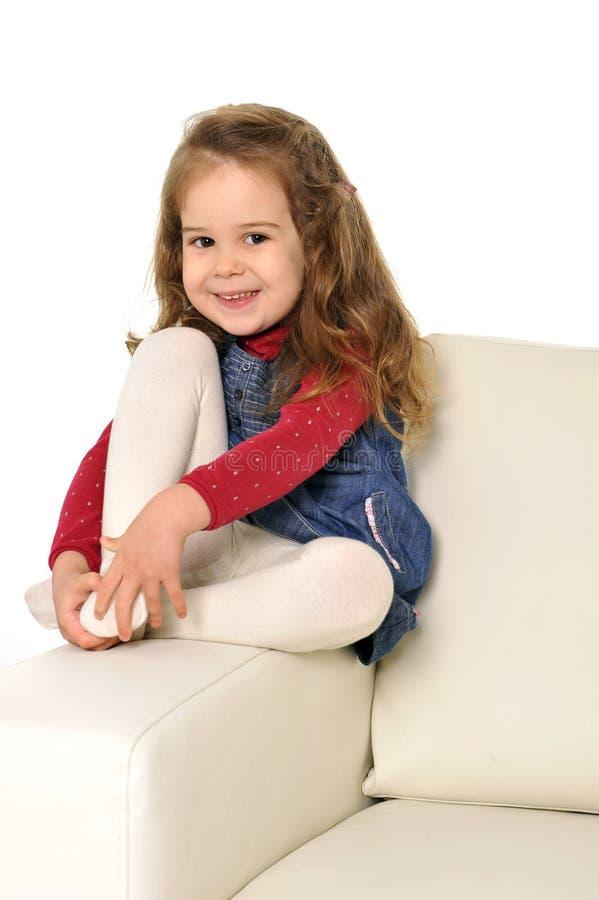有长的头发的愉快的可爱的小女孩坐长沙发的胳膊 免版税图库摄影