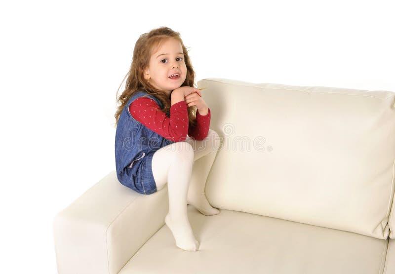 有长的头发的愉快的可爱的小女孩坐长沙发的胳膊 库存照片