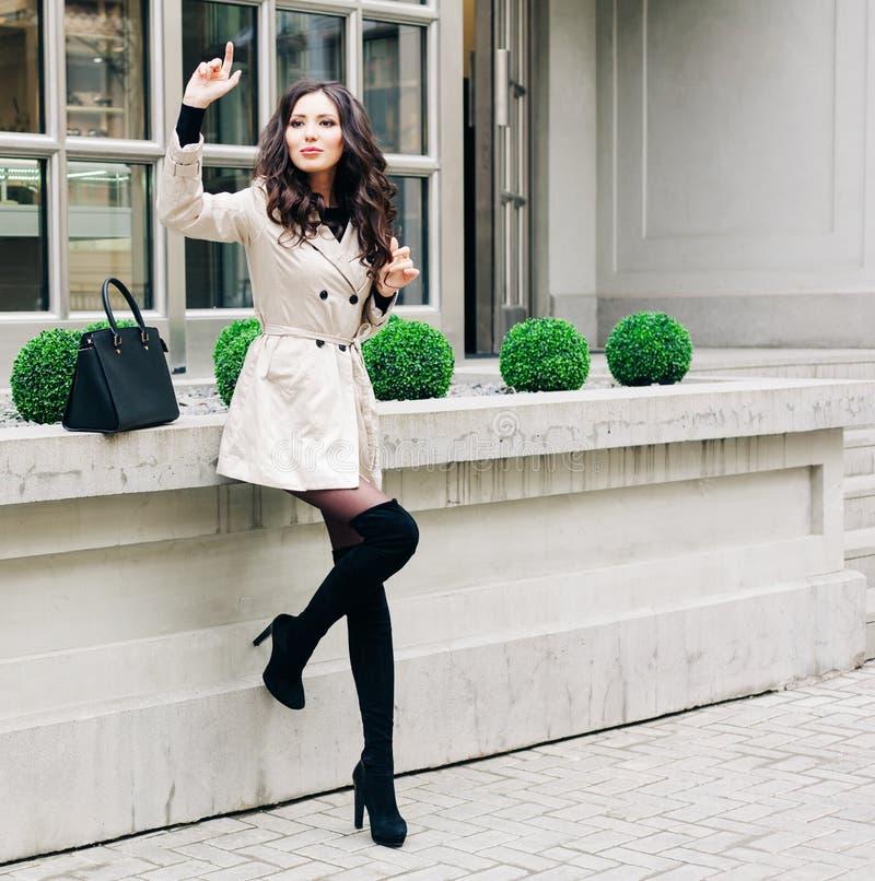 有长的头发的时兴的深色的女孩,穿戴在雨衣,与脚跟的高黑起动有手袋等待的 免版税库存图片