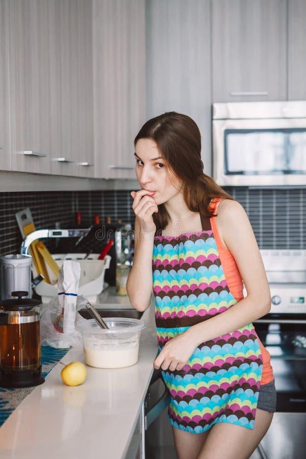 有长的头发的白种人妇女女孩烹调食物薄煎饼的站立在厨房里 免版税库存图片