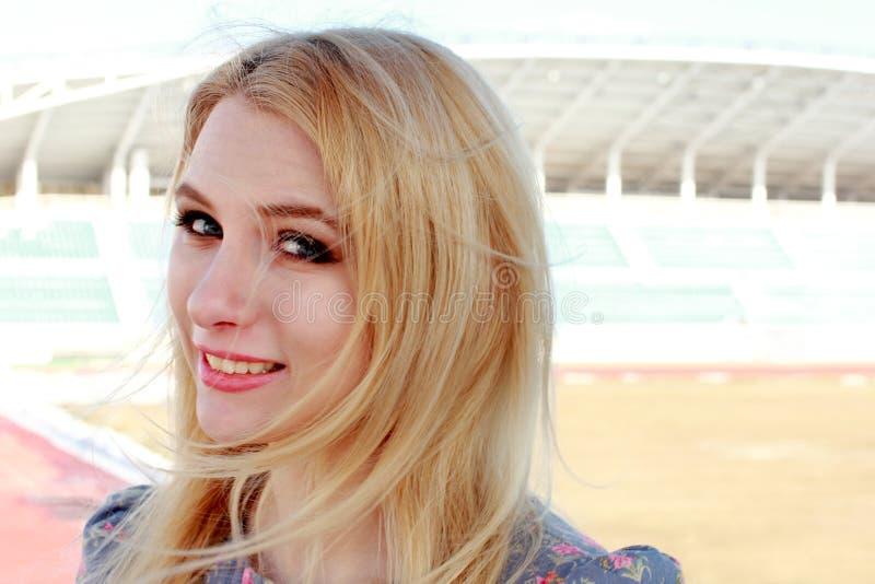 有长的头发的罚款金发碧眼的女人在轻的白色backgro的淡紫色礼服 免版税库存图片