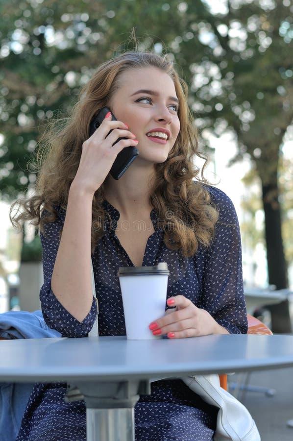 有长的头发的美丽的女孩谈话在手机 免版税库存照片