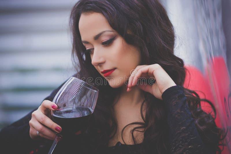 有长的头发的美丽的妇女喝红葡萄酒的在餐馆 免版税库存图片