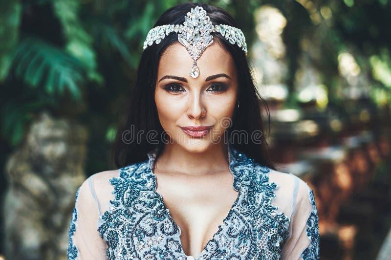 有长的头发的美丽的深色的女孩有在头的一个冠的 免版税库存图片