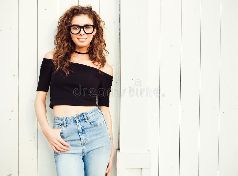 有长的头发的美丽的年轻深色的妇女在摆在样式70的上面和牛仔裤穿戴了在一个温暖的夏天晚上  免版税库存图片