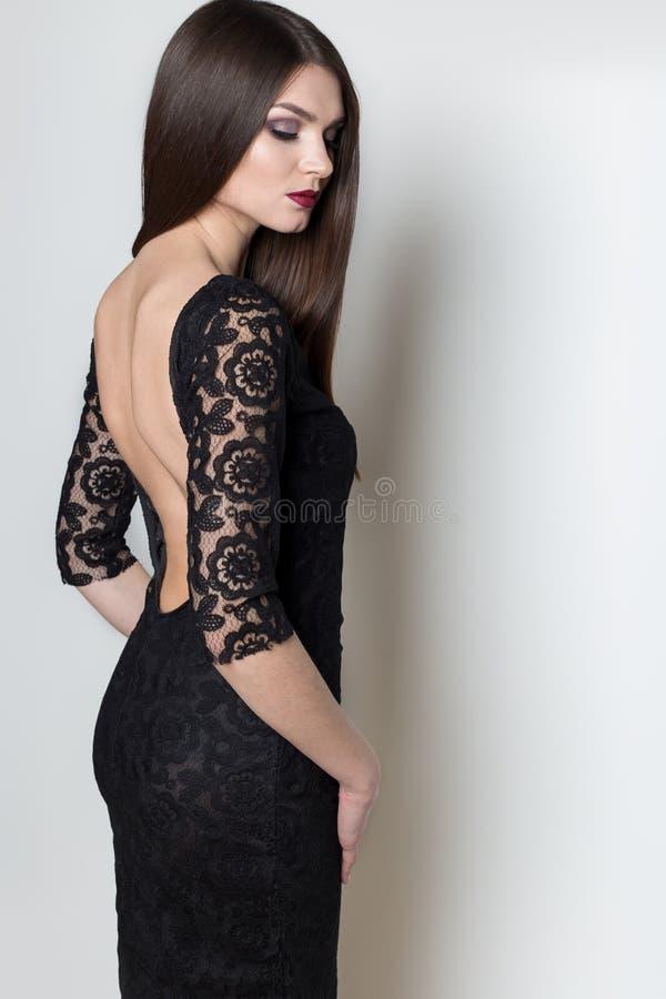 有长的头发的,在一件黑晚礼服的明亮的晚上构成性感的美丽的端庄的妇女在白色背景的演播室 免版税库存照片