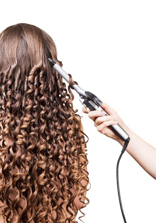 有长的头发的,在白色的手理发师烫发钳妇女 免版税库存照片