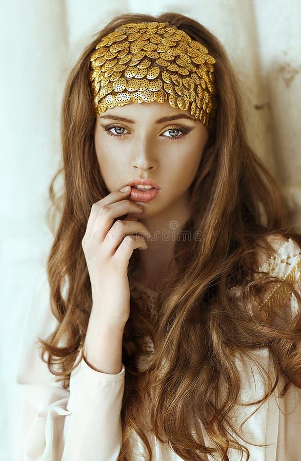 有长的头发的年轻美丽的女孩和金子塑造冠 免版税库存图片