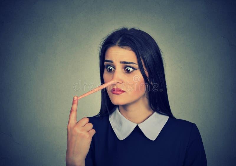 有长的鼻子的担心的妇女 说谎者概念 库存照片