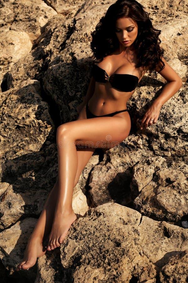 有长的黑暗的卷发佩带的比基尼泳装和海滩分类的性感的妇女 库存照片