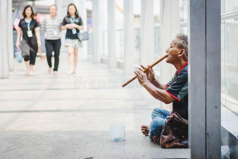 有长笛的叫化子人乞求为在街道上的金钱 免版税库存图片