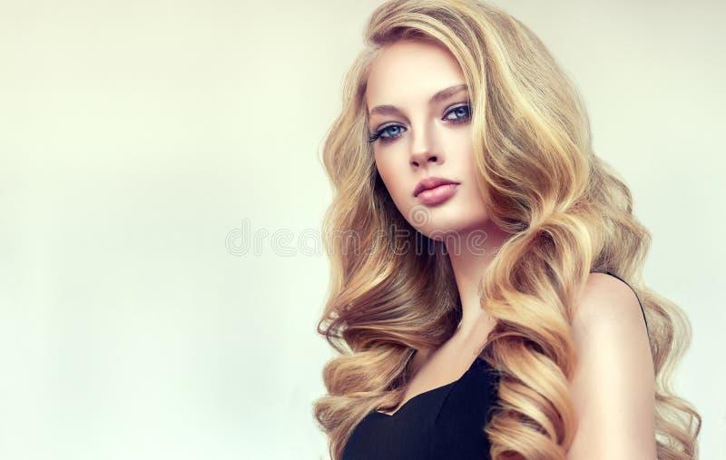 有长篇,发光和卷曲发型的金发妇女 卷曲的头发 免版税库存照片