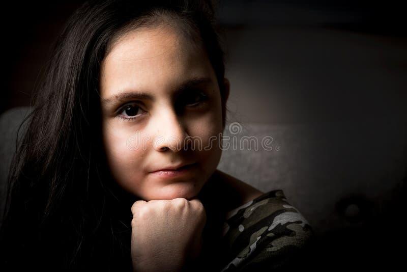 有长黑发摆在的逗人喜爱的深色的女孩 免版税库存照片
