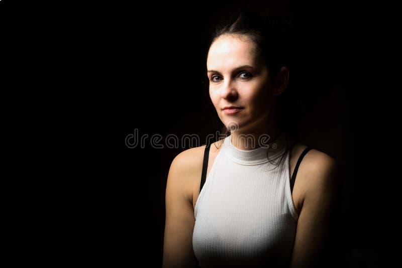 有长黑发摆在的逗人喜爱的深色的妇女 库存图片