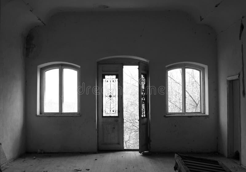 有门和两个窗口的被放弃的室 免版税库存照片