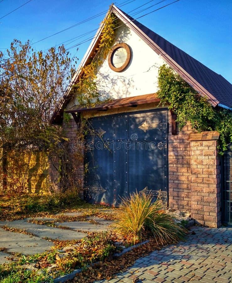 有门的老房子在秋天 在老房子下落的黄色的庭院里离开 免版税库存图片