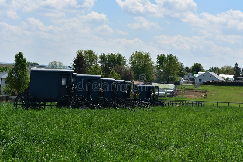 有门诺派中的严紧派的停放的儿童车和推车的农场 免版税库存照片