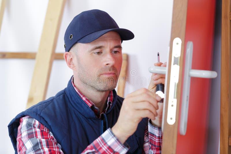 有门锁的木匠在锁过程设施时到木门里 图库摄影