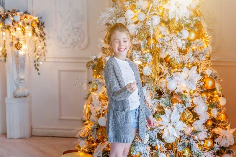 有闪烁发光物的女孩在圣诞树附近在家 库存图片