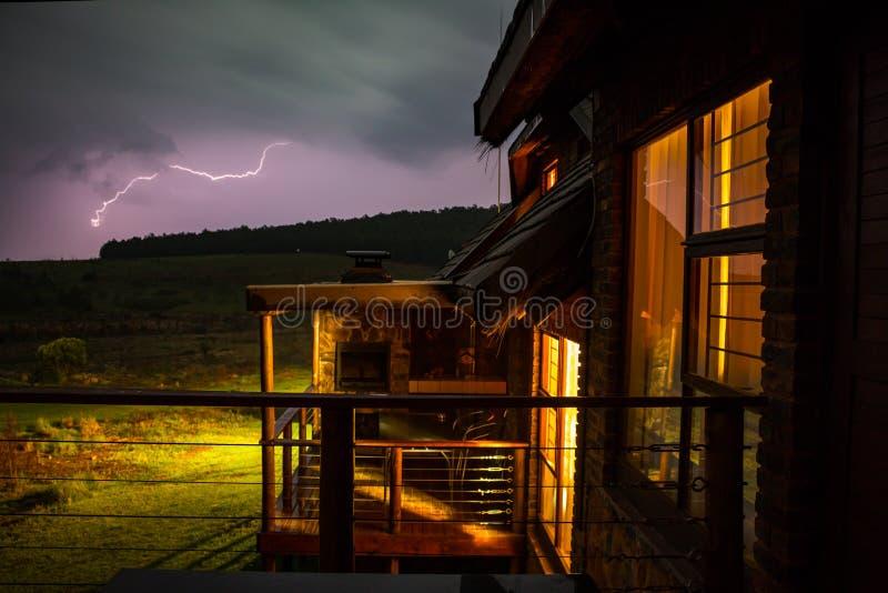 有闪电的山小屋在背景中 库存图片