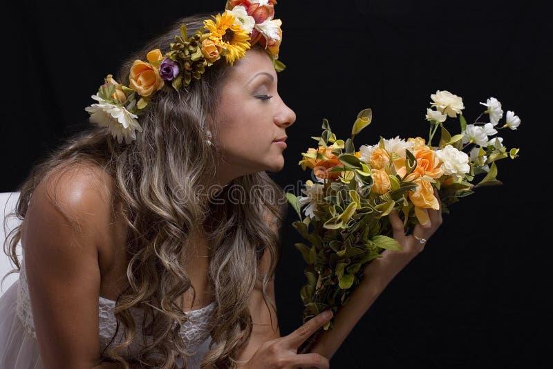 有闭上的眼睛的少妇,嗅到花花束  库存图片