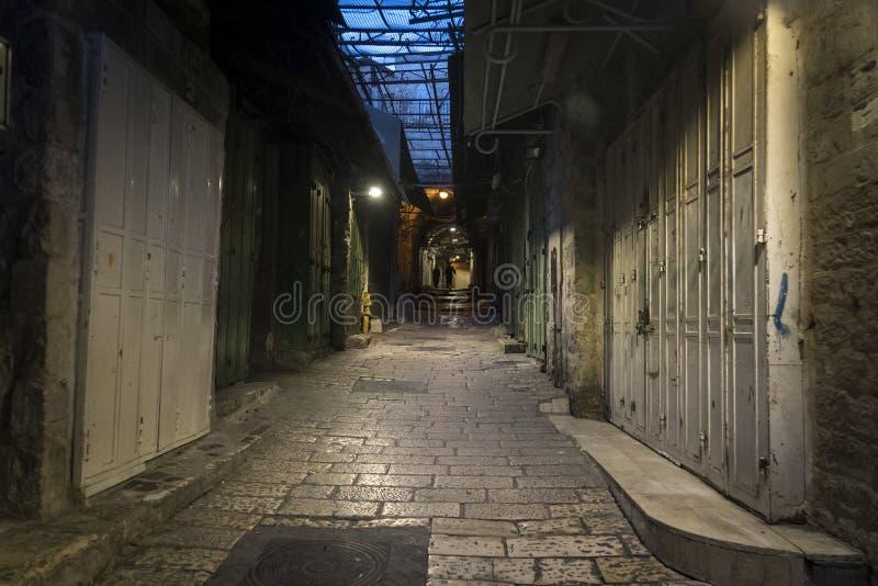 有闭合的白色门的狭窄的小巷在每边和两个黑暗的人的图在距离 有石头的离开的都市路 库存照片