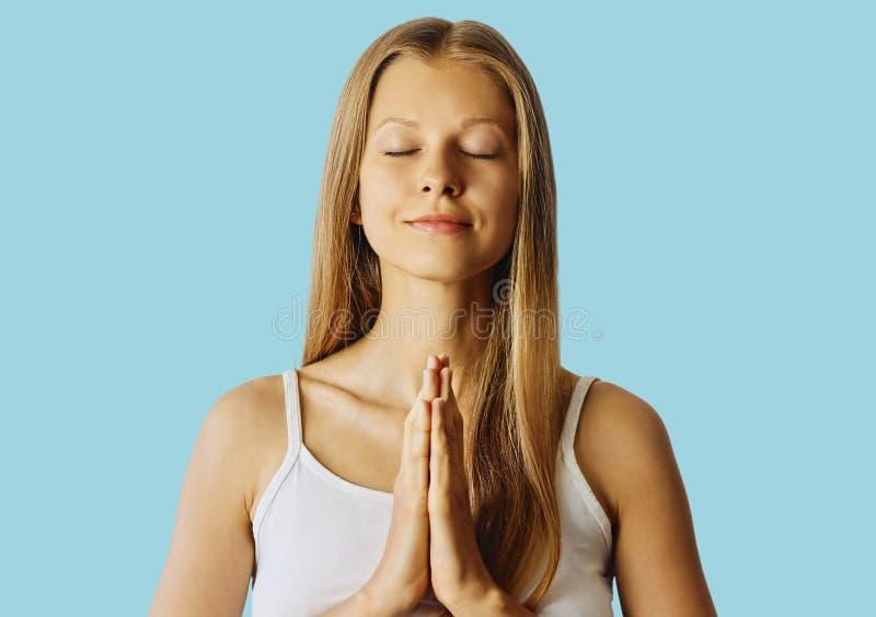 有闭合的眼睛和手的年轻女人在祈祷的姿态 凝思、平衡和心境的安宁概念 在蓝色 免版税图库摄影