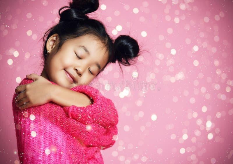有闭合的眼睛的亚裔孩子女孩在桃红色毛线衣拥抱和梦想 金黄亮晶晶的小东西 图库摄影